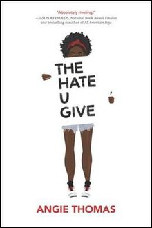 Cover art for the novel The Hate U Give, published in 2017. The cover art depicts a young African-American female teenager holding a title card with the novel's title; the title card obscures the entirety of the teenager's torso, and the only visible clothing includes a red hairband, blue denim cut-off shorts, and white athletic shoes.