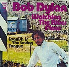 "A 7-inch single cover showing Bob Dylan in front of a field. The words ""Bob Dylan"", ""Watching The River Flow"", and ""Spanish Is The Loving Tongue"" appear over the picture."