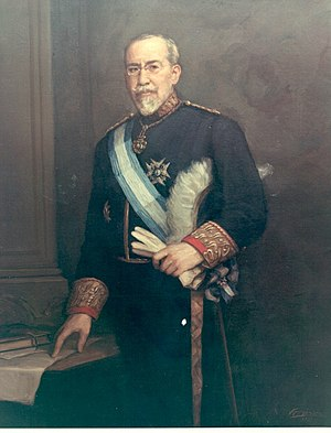 Wenceslao Ramírez de Villa-Urrutia, 1st Marquis of Villa-Urrutia -  alt=Standing portrait of 60-ish man with a white beard, mustache, and receding hairline, in circa-1900 formal dress with glasses, a high collar, a star-shaped badge on his jacket, and a blue and white sash, holding a glove and loosely pointing to a paper on a table.