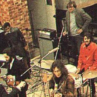 Mal Evans -  Evans (with hand on hip, behind Ringo Starr) on the Apple Records rooftop during filming for Let It Be.