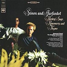 """Zwei Männer sitzen und schauen den Betrachter an.  Der in der Mitte hat gelbes Haar und ein blaues Hemd und Jeans, während der Mann links von ihm schwarze Haare hat, die sich in den Hintergrund einfügen, und ein weißes Hemd.  Nur die rechte Seite des Gesichts des zweiten Mannes ist sichtbar.  Blumen stehen im Vordergrund der Bilder.  Das Recht des ersten Mannes steht in der Schrift """"Simon und Garfunkel"""" und darunter """"Petersilie, Salbei, Rosmarin und Thymian"""".  Oben links und in der Mitte oben im Bild befinden sich Symbole."""
