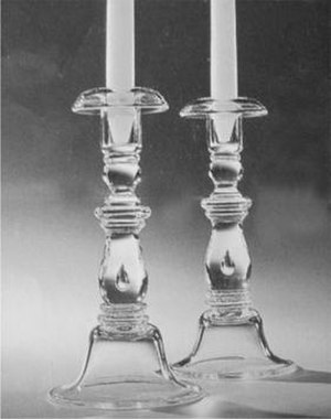 Steuben Glass Works - An example of Steuben Glass design during the Houghton era is the Balustrade Candlestick set, which mimics a classical balustrade. Of special note is the hallmark of the perfectly formed tear drop air bubble suspended in the design.