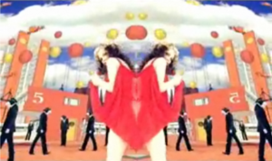 Strict Machine - Alison Goldfrapp in a kaleidoscopic setting containing Archigram-style buildings.