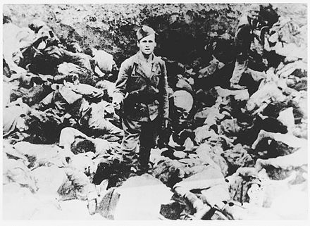 An Ustase guard stands among the bodies of prisoners murdered in the Jasenovac concentration camp, 1942 Ustasa guard, Jasenovac.jpg