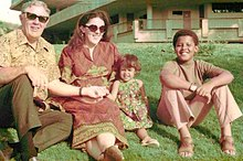 A young boy possibly in his early teens, a younger girl (about age five), a woman and an elderly man sit on a lawn wearing contemporary c.-1970 attire. The adults wear sunglasses and the boy wears sandals.