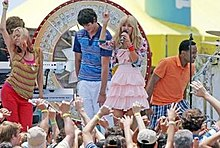 A blond teenager with a pink dress and metallic jacket singing into a microphone. Behind her are people dancing in an outside stage.