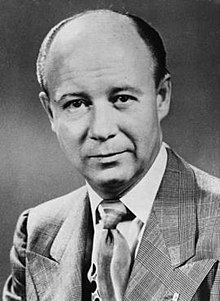 A black-and-white portrait photograph of a mostly bald middle-aged man in a dapper suit.
