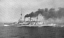 A large battleship plows through the water at high speed, thick black smoke pours from the smoke stacks