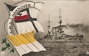 "Superimposed on a photo of a large gray warship are a large white life-preserver, on which is printed the name ""S.M.S. Hannover"" in black letters, the black and white flag of the German Navy, and a white and yellow flag; thick black smoke drifts from the ship's three smokestacks."
