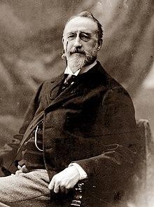 Homme blanc d'âge moyen assis, avec une moustache de longueur moyenne et une barbe soignée, regardant avec bienveillance vers la caméra