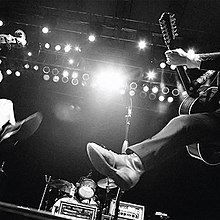 A black-and-white worms-eye-view photo of two string players jumping in the air in front of a drum kit