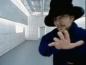 "Virtual Insanity - Jay Kay in a moving futuristic room in the ""Virtual Insanity"" music video. The video received critical acclaim from critics for its visual effects."