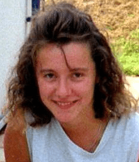 A Caucasian female, probably in her late teens, with light brown hair and brown eyes wearing a white sleeveless shirt looking at the camera and smiling. Visible in the background are a red-and-white patio, a lawn and a white-painted building with an attached black drainpipe.
