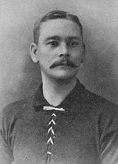 Head and upper torso of a white man with a moustache wearing a dark sports shirt.