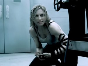 "Die Another Day (song) - Madonna in a scene from the music video of ""Die Another Day"" showing her wrapping phylacteries around her arm, while hiding behind the electric chair."