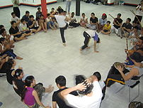 A sit-down roda held in a capoeira academy.