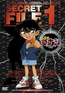 The DVD cover shows a young boy with black hair and glasses, wearing a blue vest with a white dress shirt showing underneath, light blue shorts, and a bow-tie. The boy is pointing his finger outside the cover accusingly. Above him in big red bold letters are the words Shonen Sunday Original Collection, Secret File Vol. 1. To the right of the boy is a bullet hole with the kanji for Meitantei Conan and under it in white letters are the words Shogakukan Video.