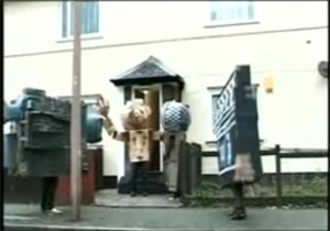 Juxtapozed with U - Three people dressed in cardboard costumes as a camcorder, microphone and clapperboard respectively, meet a fourth person with a large cardboard head and arms (seen here in the centre exiting the house) in the Fukme 99 video.