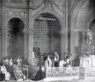 elaborate stage set with large cast, with a nun centre stage