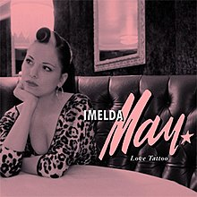 "A pink-saturated picture of a woman sitting at a diner table. White text reads ""Imelda May Love Tattoo."""
