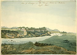 Watercolour of a river and a fort. The river's flow is disturbed by some small rocks; a hidden creek or stream runs into the river in the foreground; a small boat has been pulled out of the water and left resting on the far bank. The fort, with six visible turrets, is built on the edge of a cliff overlooking the river. Hills line the distant background.