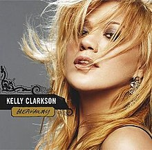 "A blonde haired woman with her hair being swept by the wind, in her right, the words ""Kelly Clarkson"" and ""Breakaway"" are printed in front of a vector scroll art."
