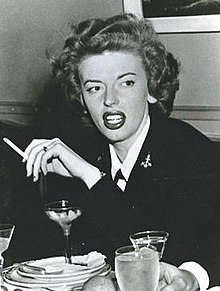 A young white woman in a black blazer. She is holding a cigarette and there is a martini glass on a table in front of her.