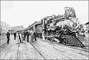 "Seattle, Lake Shore and Eastern Railway - ""Seattle, Lake Shore and Eastern Railway's Engine No. 2, the D.H. Gilman, photographed on Independence Day, 1895"", ""despite the rain"", at Columbia Street Station on Railroad Avenue built on pilings over filled mudflat, now Western Avenue. The occasion had a holiday excursion to Sumas. The quote is from the foreground of the image."