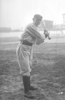 A man wearing a baseball uniform standing truned to his left poised to swing a baseball bat.