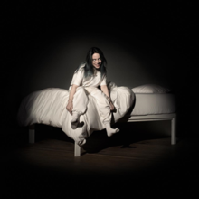 Eilish sits on the edge of a white bed, in front of a dark background. She wears white clothing, while smiling at the camera.