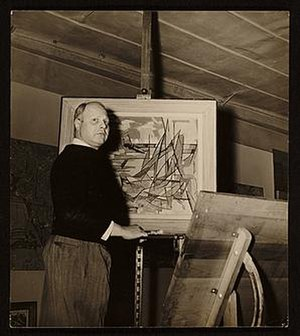 Carl Holty - Carl Holty with one of his paintings, ca. 1950, unidentified photographer. Carl Holty papers, Archives of American Art, Smithsonian Institution
