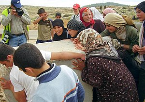 Christian Peacemaker Teams - Palestinians remove a roadblock while a member of CPT stands behind them.