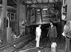 A subway car, lying twisted around a pole after a derailment. In front of the subway car, two men are investigating the wreckage.