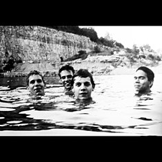 A black-and-white photograph of Slint standing in tall water with only part of their faces visible