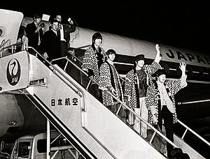 The Beatles' 1966 tour of Germany, Japan and the Philippines - The Beatles descending from the aircraft at Tokyo's Haneda Airport, dressed in matching JAL coats. The band members wave at what they believe to be a crowd of fans, unaware of the strict security measures imposed by the Japanese authorities towards all members of the public.