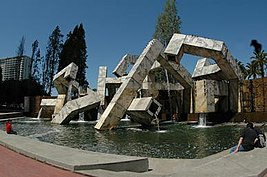 A series of angular, jumbled, concrete pieces, with water running through them, set in a pool.