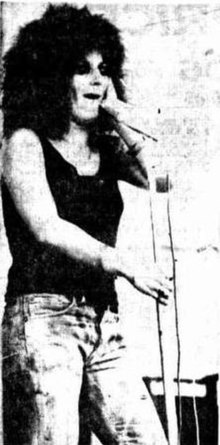 A 20-year-old woman is singing at a microphone and staring into the distance. She wears a dark singlet-top and jeans and has her hair in an afro. Her right arm is slightly bent as she holds the microphone stand. Her left hand is up near her left cheek.