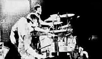"""Who Really Cares (Featuring the Sound of Insanity) - Powderfinger drummer Jon Coghill (right) and touring pianist Lachlan Doley (left) in the music video for """"Who Really Cares"""", featuring high contrast optical filters."""