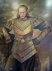 An image of Wilhelm von Homburg in character as Vigo the Carpathian. An imitation canvas painting of a middle-aged white man with shoulder-length dark blonde hair. He is scowling while looking forward. The man is shown wearing ancient armor that covers most of his body.