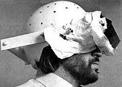 A set of mirrors attached via a harness and a helmet to a man's head; the mirrors show the man his own body reflected upside down, and a covering blocks his view of anything other than the mirror.