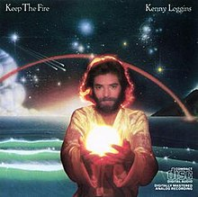 Kenny Loggins, a long-haired bearded man, holding football-sized glowing sphere, standing in front of fantastic space scene above an ocean.