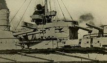 A large warship's bridge and two gun turrets