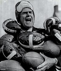 A man in a leather helmet with his mouth open, holding several footballs and helmets