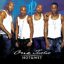 An image of four black men wearing white tank tops and blue jeans standing in front of a blue background with the group's logo.