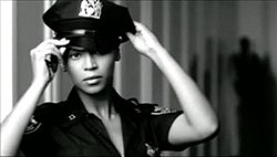Beyoncé acting like a police officer. She wears the uniform of the New York Police, and she is putting the cap. On the background, a striped wall is visible.