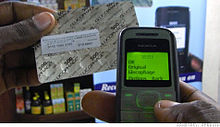 A drug package with Sproxil label and phone showing SMS reply.