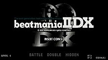 "Two gears imprinted with ""dj"" and ""II"" are placed above the widened letters ""DX"" to form a silver metallic logo over a black background. It is partially covered by the slab-serif Beatmania IIDX logo, accompanied by Konami's brief copyright information and the dark blue text ""The ultimate system beatmania deluxe version."" ""Insert Coins(s)"" appears slightly off the center of the title screen, and ""Level 4"", ""Battle Double Hidden"", and ""0/1 0/2 coin(s)"" are seen at its bottom side."
