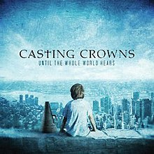 A boy is sitting on a ledge overlooking a cityscape, a megaphone positioned on his left-hand side. The name of the album is positioned above his head, with the logo of the band stationed above that; both the album title and band name are written in capital letter, while the 'T' in 'Casting Crowns' is replaced by a cross.