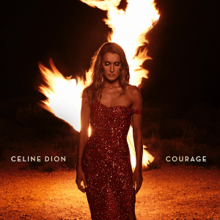 An image of a woman, in a dress, standing in front of a fire blaze