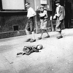 A child dying in the streets of the crowded Warsaw Ghetto, where hunger and disease killed 43,000 in 1941 alone.